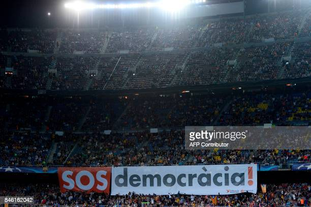 Barcelona's fans display a giant banner reading 'SOS Democracy' before the UEFA Champions League Group D football match FC Barcelona vs Juventus at...