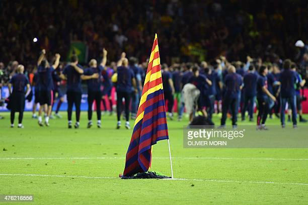 Barcelona's flag is seen on the pitch as players celebrate in the background after winning the UEFA Champions League Final football match between...