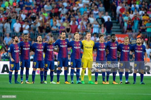 Barcelona's football players observe a minute of silence as they wear jerseys reading 'Barcelona' instead of their names to pay tribute to the...
