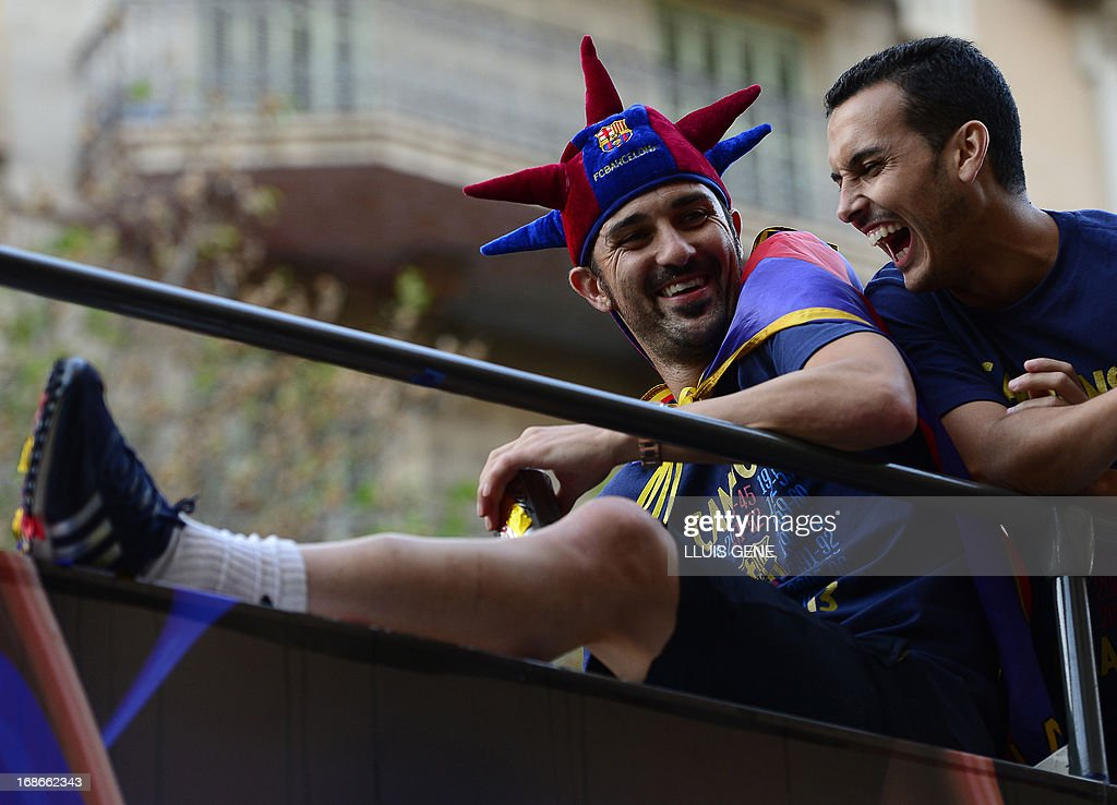 Barcelona's forward David Villa (L) and Barcelona's forward Pedro Rodriguez react as they and their teammates parade on a bus through a crowd of supporters celebrating in the streets of Barcelona on May 13, 2013, two days after their team won the Spanish league. The Catalans didn't even need to set foot on the pitch to seal the title on May 11 as Real Madrid's 1-1 draw with Espanyol meant Barca had already been crowned champions before their 2-1 win over Atletico Madrid on May 12, 2013.