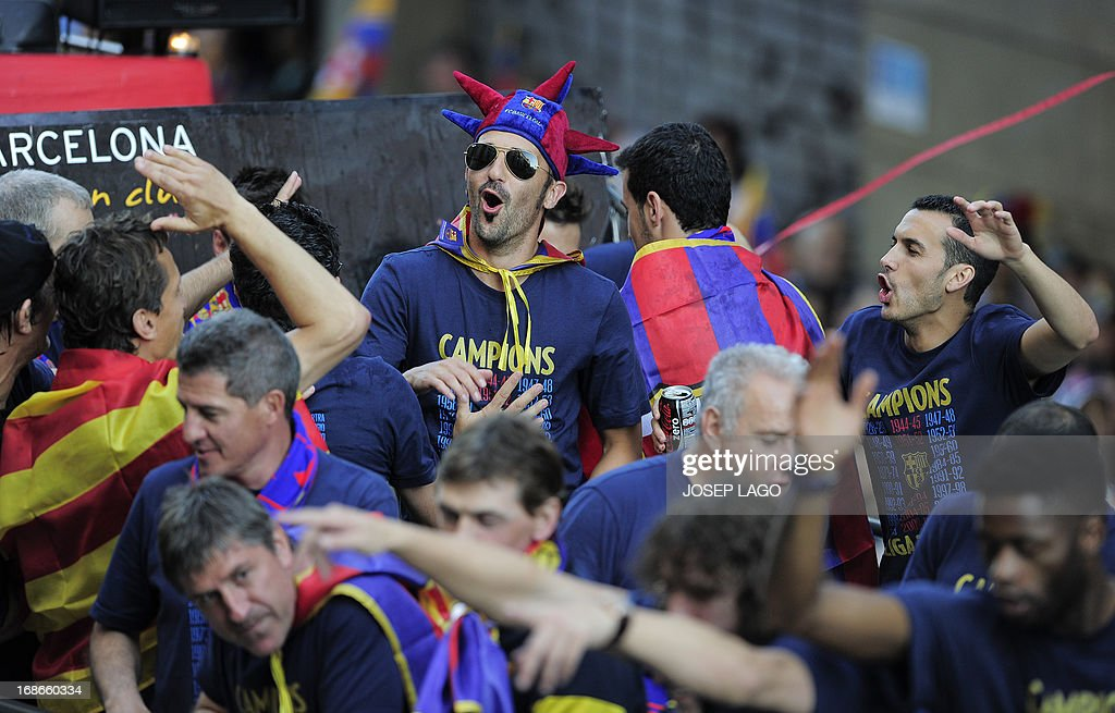 Barcelona's forward David Villa (C) reacts as he and his teammates parade on a bus through a crowd of celebrating supporters in the streets of Barcelona on May 13, 2013, two days after their team won the Spanish league. The Catalans didn't even need to set foot on the pitch to seal the title on May 11 as Real Madrid's 1-1 draw with Espanyol meant Barca had already been crowned champions before their 2-1 win over Atletico Madrid on May 12, 2013.