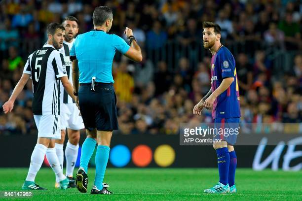 Barcelona's forward from Argentina Lionel Messi receives a yellow card from referee during the UEFA Champions League Group D football match FC...