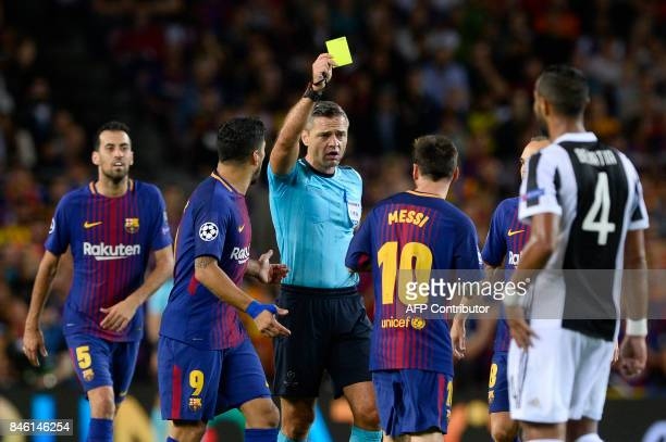 Barcelona's forward from Argentina Lionel Messi receives a yellow card during the UEFA Champions League Group D football match FC Barcelona vs...