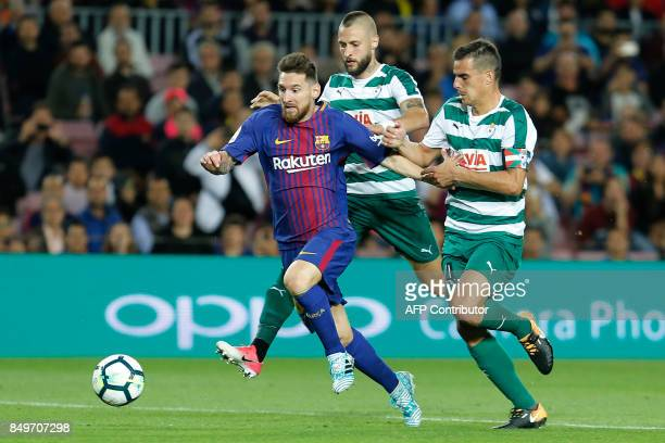 Barcelona's forward from Argentina Lionel Messi runs with the ball besides Eibar's defender from Spain David Junca during the Spanish league football...
