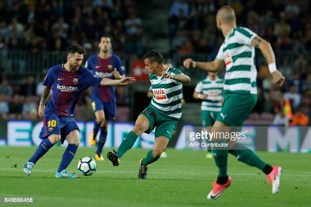 Barcelona's forward from Argentina Lionel Messi vies with Eibar's midfielder from Spain Daniel Garcia Carrillo during the Spanish league football...