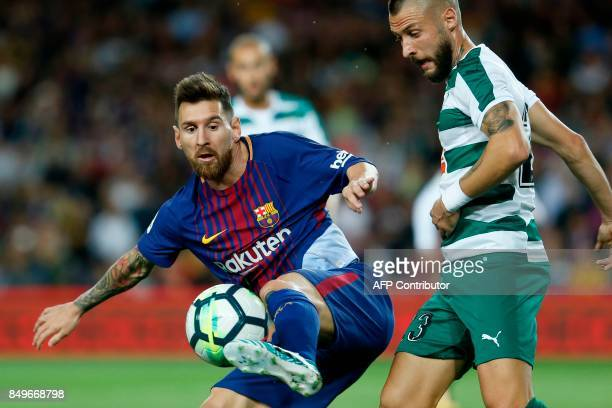 Barcelona's forward from Argentina Lionel Messi vies with Eibar's defender from Spain David Junca during the Spanish league football match FC...