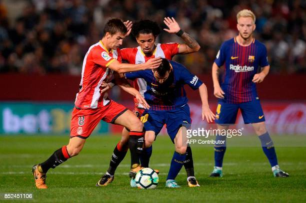 Barcelona's forward from Argentina Lionel Messi vies with Girona's midfielder Pere Pons and Girona's midfielder Alex Granell during the Spanish...