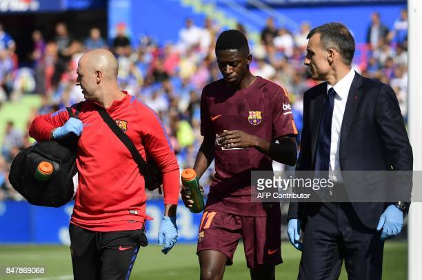 Barcelona's forward from France Ousmane Dembele walks with the team's doctor during the Spanish league football match Getafe CF vs FC Barcelona at...