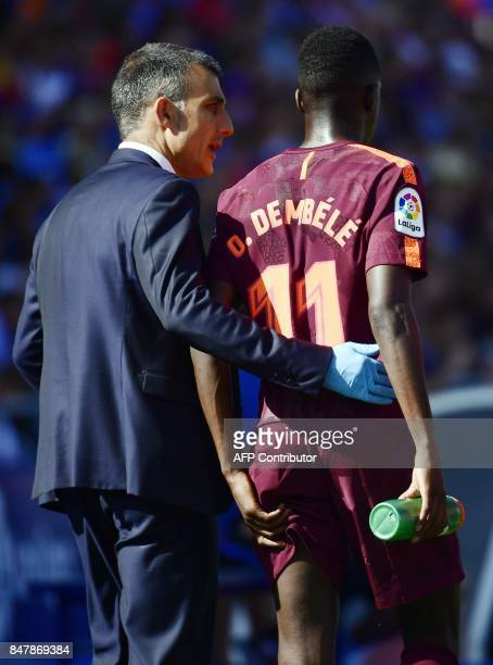 Barcelona's forward from France Ousmane Dembele walks with the team's doctor after resulting injured during the Spanish league football match Getafe...