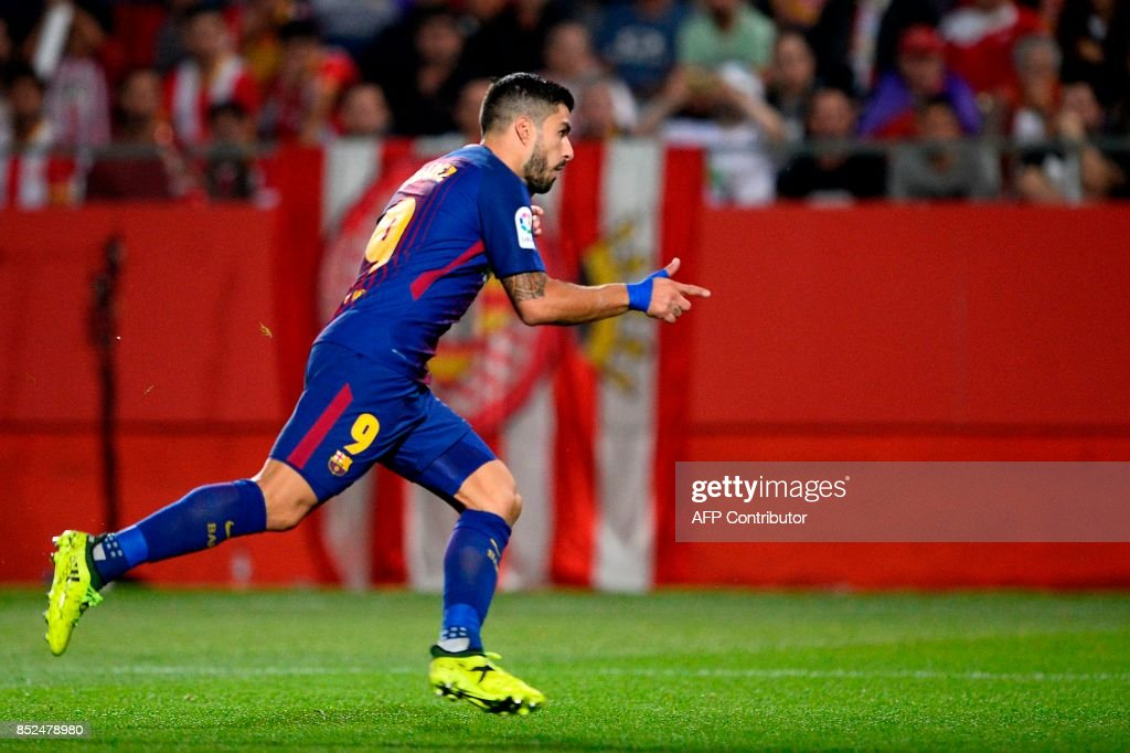 Barcelona's forward from Uruguay Luis Suarez celebrates after scoring during the Spanish league football match Girona FC vs FC Barcelona at the Montilivi stadium in Girona on September 23, 2017. / AFP PHOTO / Josep LAGO