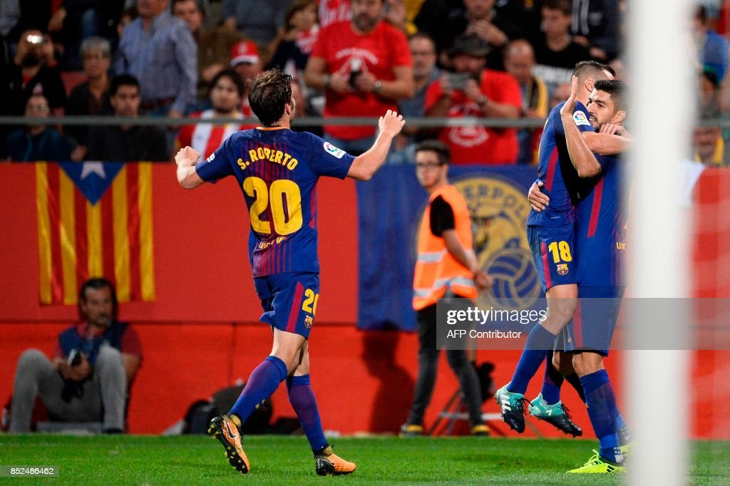 Barcelona's forward from Uruguay Luis Suarez (R) celebrates with Barcelona's defender from Spain Jordi Alba (C) and Barcelona's midfielder from Spain Sergi Roberto after scoring during the Spanish league football match Girona FC vs FC Barcelona at the Montilivi stadium in Girona on September 23, 2017. / AFP PHOTO / Josep LAGO
