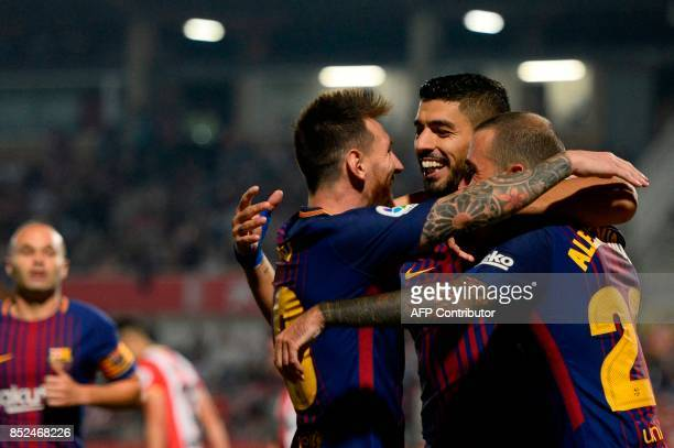 Barcelona's forward from Uruguay Luis Suarez celebrates with Barcelona's forward from Argentina Lionel Messi and a teammate after scoring during the...