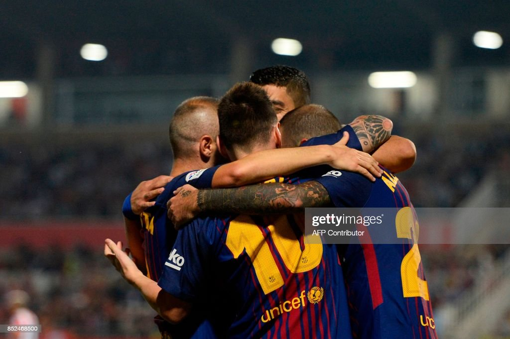 Barcelona's forward from Uruguay Luis Suarez (back) celebrates with teammates after scoring during the Spanish league football match Girona FC vs FC Barcelona at the Montilivi stadium in Girona on September 23, 2017. / AFP PHOTO / Josep LAGO