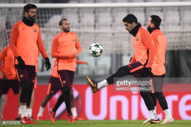 Barcelona's forward Luis Suarez from Uruguay and Barcelona's Spanish defender Gerard Pique attend a training session on the eve of the UEFA Champions...