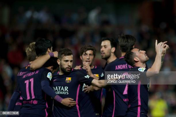 Barcelona's forward Paco Alcacer celebrates a goal with teammates during the Spanish league football match Granada FC vs FC Barcelona at Nuevo Los...