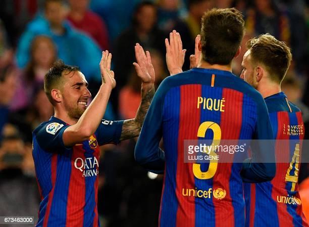 Barcelona's forward Paco Alcacer celebrates with Barcelona's defender Gerard Pique and Barcelona's Croatian midfielder Ivan Rakitic after scoring a...