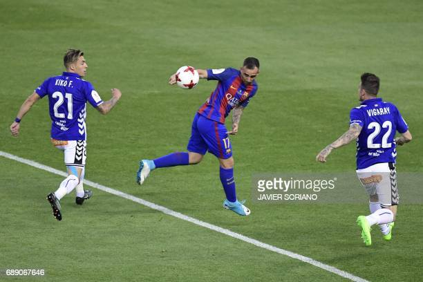 Barcelona's forward Paco Alcacer vies with Deportivo Alaves' defender Kiko Femenia and Deportivo Alaves' defender Carlos Vigaray during the Spanish...