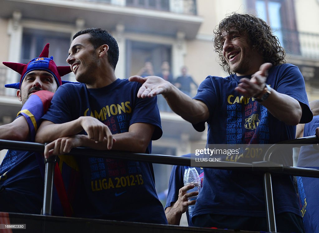 Barcelona's forward Pedro Rodriguez (C) and Barcelona's midfielder and captain Carles Puyol (R) react as they and their teammates parade on a bus through a crowd of supporters celebrating in the streets of Barcelona on May 13, 2013, two days after their team won the Spanish league. The Catalans didn't even need to set foot on the pitch to seal the title on May 11 as Real Madrid's 1-1 draw with Espanyol meant Barca had already been crowned champions before their 2-1 win over Atletico Madrid on May 12, 2013.