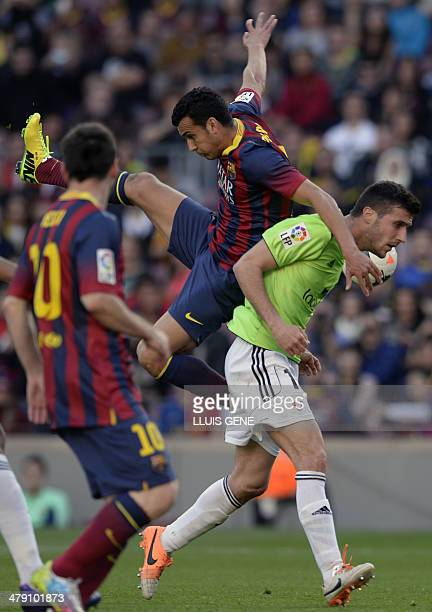 Barcelona's forward Pedro Rodriguez vies with Osasuna's midfielder Oier Sanjurjo during the Spanish league football match FC Barcelona vs Osasuna at...