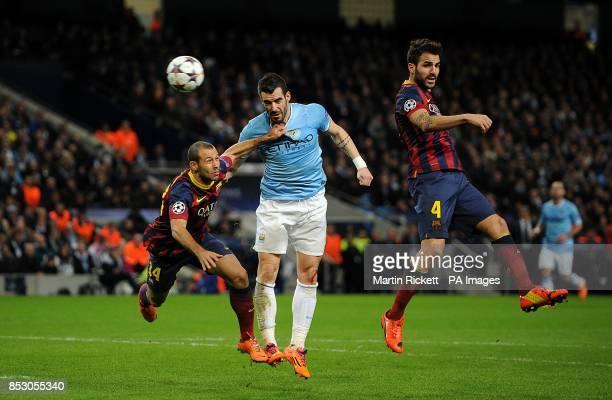 Barcelona's Francesc Fabregas and Javier Mascherano battle for the ball with Manchester City's Alvaro Negredo