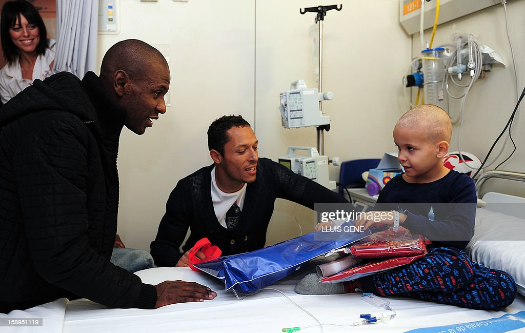 Barcelona's French defender Eric Abidal (L) and Barcelona's Brazilian defender Adriano (C) give presents to Ander (R) during a visit at the Hospital Vall d'Hebron in Barcelona on January 4, 2013.