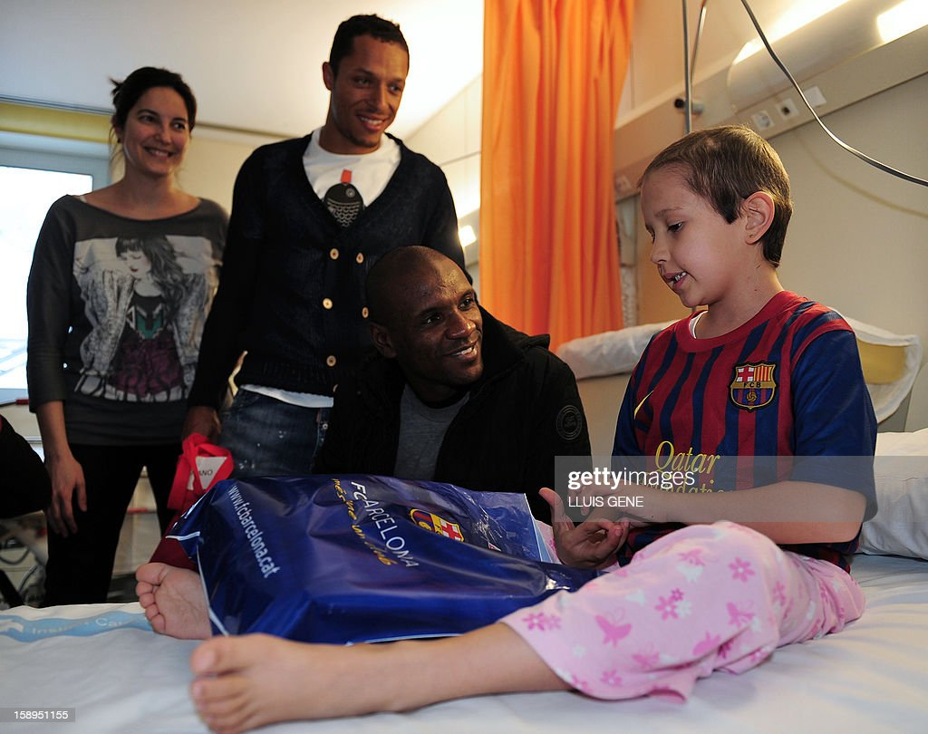 Barcelona's French defender Eric Abidal (2nd R) and Barcelona's Brazilian defender Adriano (2nd L) talk to Maria during a visit at the Hospital Vall d'Hebron in Barcelona on January 4, 2013. AFP PHOTO / LLUIS GENE