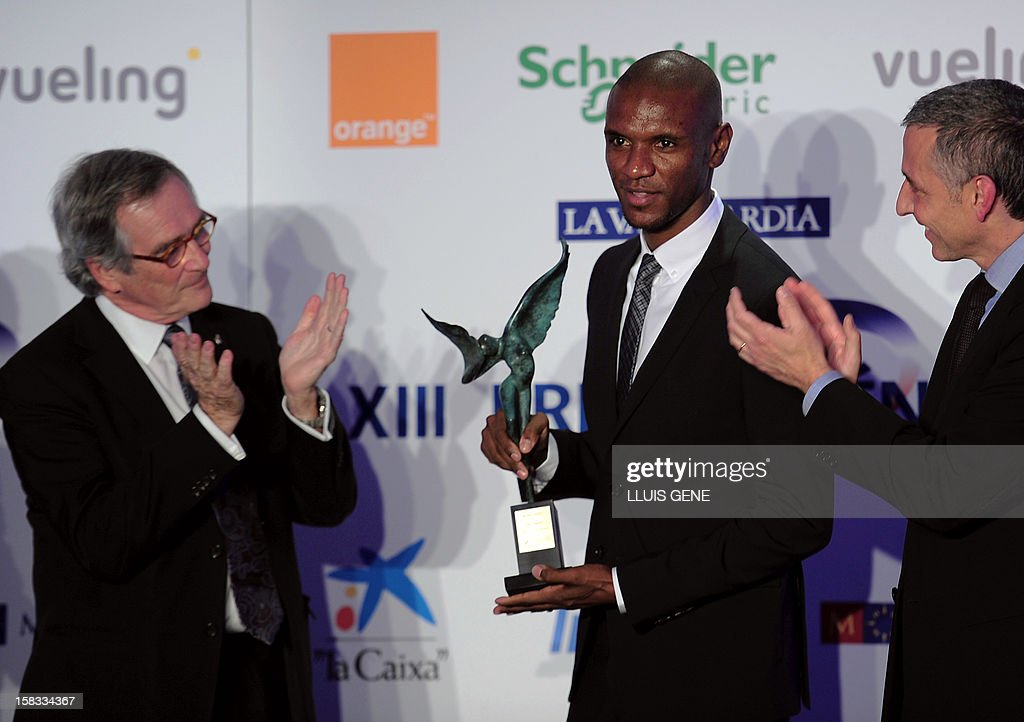 Barcelona's French defender Eric Abidal (C) poses with the XIII Prix Pyrenees trophy after receiving the award from Barcelona's mayor Xavier Trias (L) in Barcelona on December 13, 2012. AFP PHOTO / LLUIS GENE