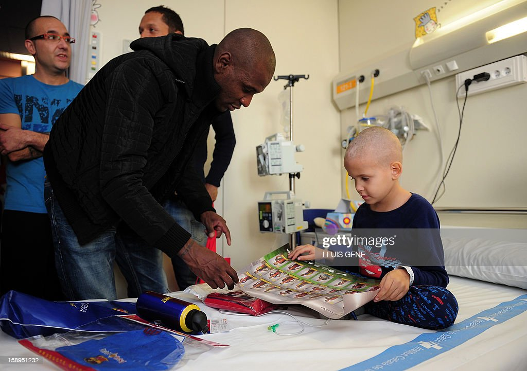 Barcelona's French defender Eric Abidal (L) speaks with Ander (R) during a visit at the Hospital Vall d'Hebron in Barcelona on January 4, 2013.