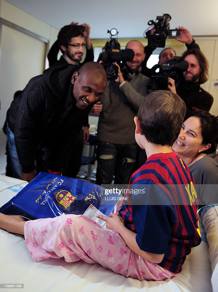 Barcelona's French defender Eric Abidal (L) speaks with Maria during a visit at the Hospital Vall d'Hebron in Barcelona on January 4, 2013.