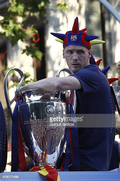 Barcelona's French defender Jeremy Mathieu sits past the Champions League trophy on a bus parading through the streets of Barcelona as the team...