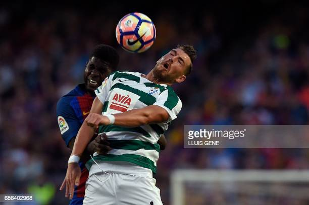 Barcelona's French defender Samuel Umtiti vies with Eibar's forward Sergi Enrich during the Spanish league football match FC Barcelona vs SD Eibar at...
