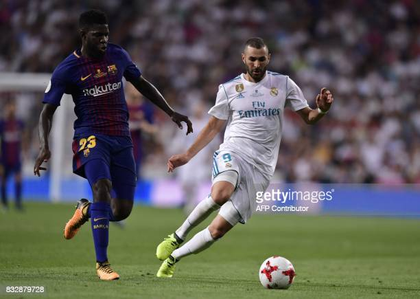 Barcelona's French defender Samuel Umtiti vies with Real Madrid's French forward Karim Benzema during the second leg of the Spanish Supercup football...