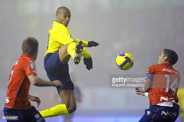 Barcelona's French forward Thierry Henry fights for the ball with Osasuna's defender Miguel Flano and defender Josecho during their Spanish league...