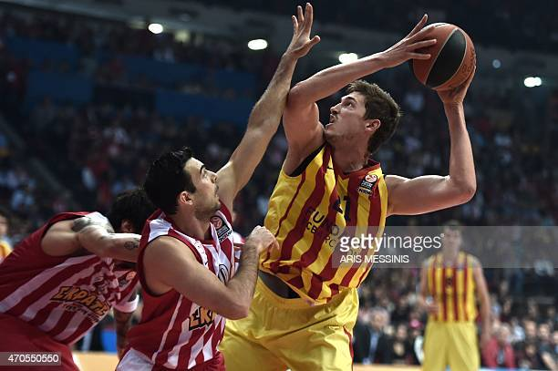 Barcelona's German center Tibor Pleiss is marked by Olympiakos' guard Kostas Sloukas during their round three playoff Euroleague basketball game at...