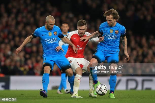 Barcelona's Javier Mascherano and Ivan Rakitic battle for the ball with Arsenal's Aaron Ramsey