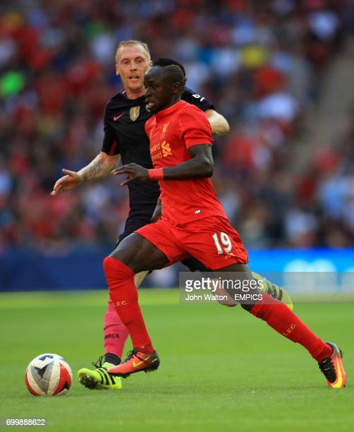 Barcelona's Jeremy Mathieu and Liverpool's Sadio Mane battle for the ball