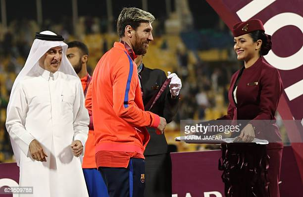 FC Barcelona's Lionel Messi receives a medal following a friendly football match between FC Barcelona and Saudi Arabia's AlAhli FC on December 13...