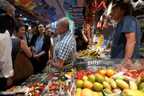 Barcelona's mayor Ada Colau chats with merchants of La Boqueria market in Barcelona on August 19 two days after a van ploughed into the crowd killing...