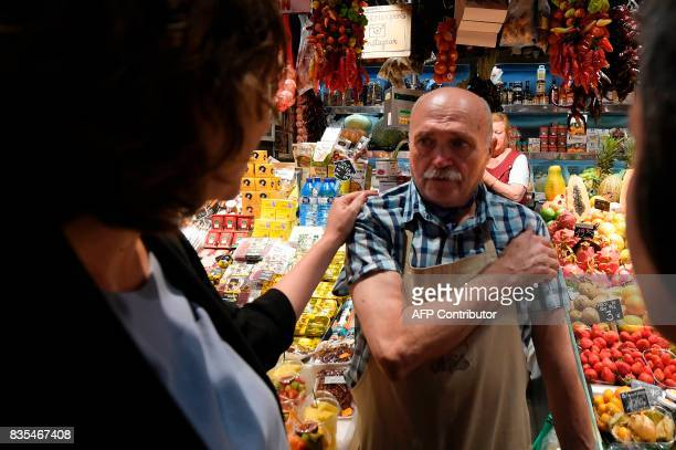 Barcelona's mayor Ada Colau comforts a merchant of La Boqueria market in Barcelona on August 19 two days after a van ploughed into the crowd killing...