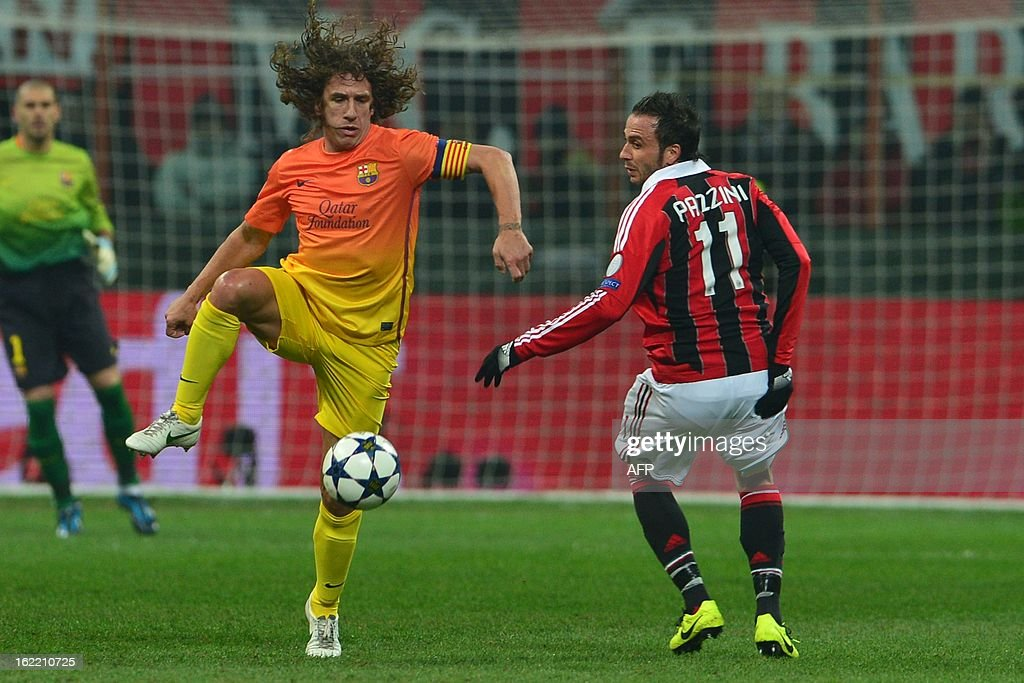 Barcelona's midfielder and captain Carles Puyol (L) challanges for the ball with AC Milan's forward Giampaolo Pazzini during the Champions League football match between AC Milan and FC Barcelona on February 20, 2013 at San Siro Stadium in Milan.