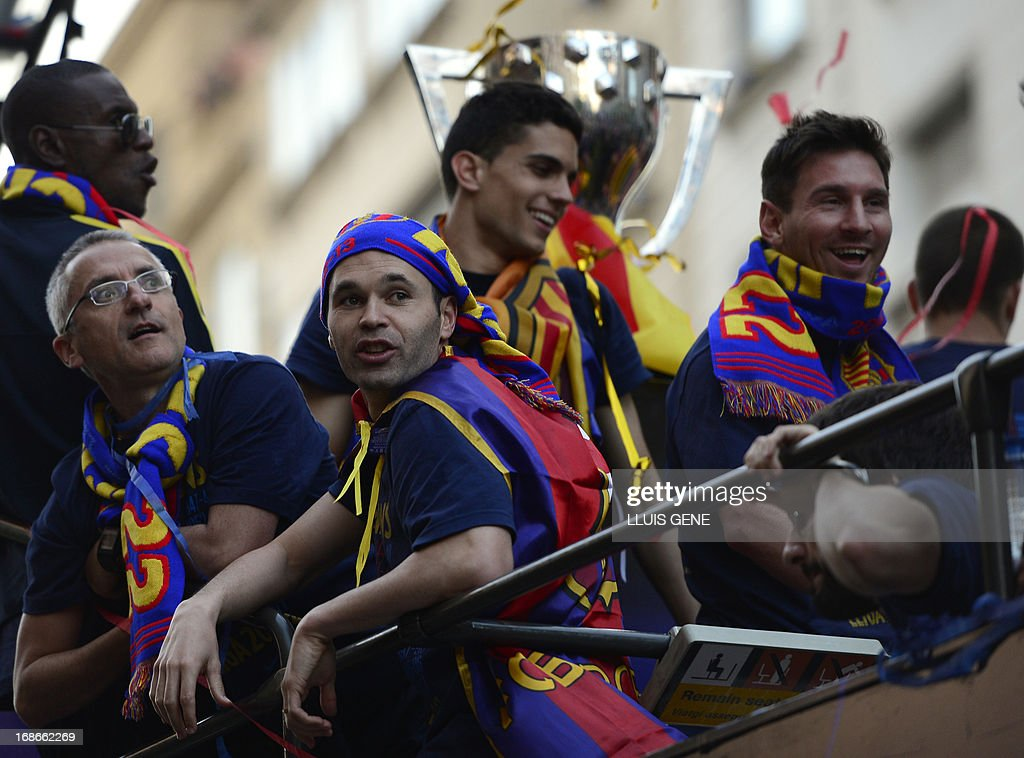 Barcelona's midfielder Andres Iniesta (2ndL) and Barcelona's Argentinian forward Lionel Messi (R) react as they and their teammates parade on a bus through a crowd of supporters celebrating in the streets of Barcelona on May 13, 2013, two days after their team won the Spanish league. The Catalans didn't even need to set foot on the pitch to seal the title on May 11 as Real Madrid's 1-1 draw with Espanyol meant Barca had already been crowned champions before their 2-1 win over Atletico Madrid on May 12, 2013.