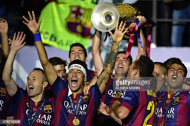 Barcelona's midfielder Andres Iniesta and Barcelona's Brazilian forward Neymar da Silva Santos Junior celebrate winth the trophy after winning the...
