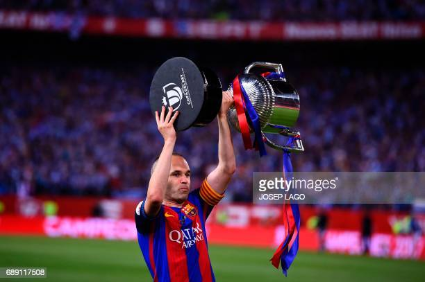 Barcelona's midfielder Andres Iniesta holds up the cup after the team won the Spanish Copa del Rey final football match FC Barcelona vs Deportivo...