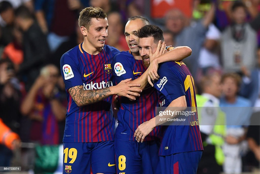 Barcelona's midfielder Andres Iniesta (C) is congratulated by his teammates Barcelona's French defender Lucas Digne (L) and Barcelona's Argentinian forward Lionel Messi (R) after scoring a goal during the Spanish league football match FC Barcelona vs Malaga CF at the Camp Nou stadium in Barcelona on October 21, 2017. / AFP PHOTO / Josep LAGO
