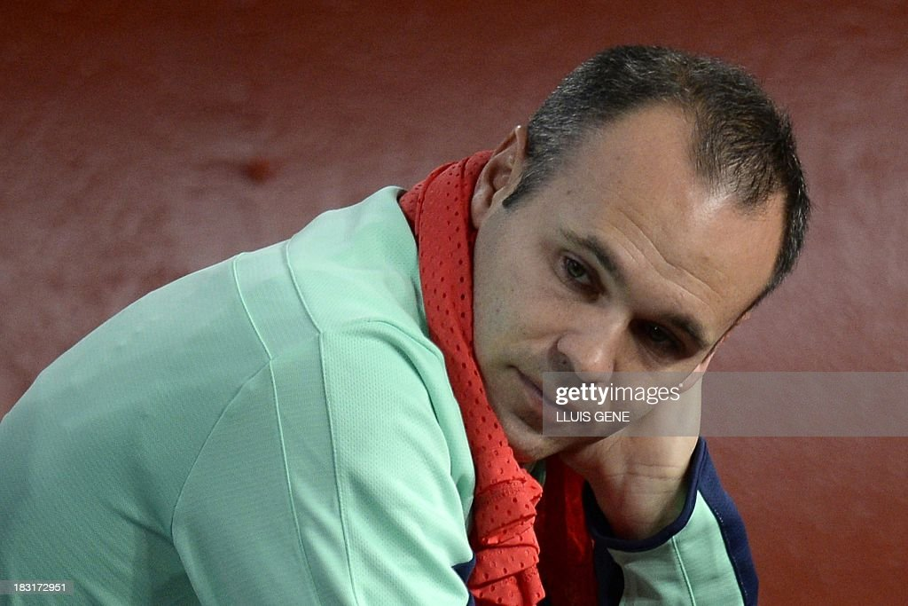 Barcelona's midfielder Andres Iniesta looks on from the bench during the Spanish league football match FC Barcelona vs Real Valladolid CF at the Camp Nou stadium in Barcelona on October 5, 2013. AFP PHOTO / LLUIS GENE