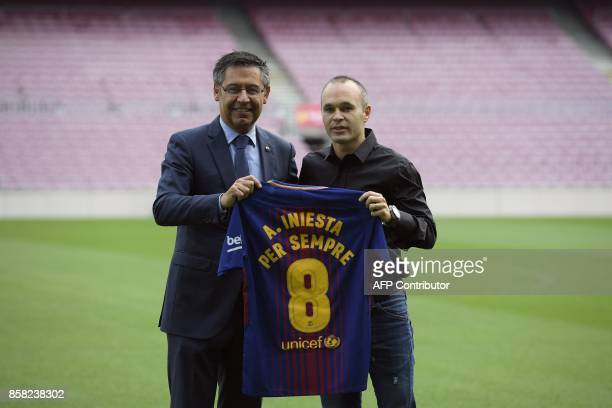 Barcelona's midfielder Andres Iniesta poses with a special Barcelona FC jersey next to the Catalan club's president Josep Maria Bartomeu after...