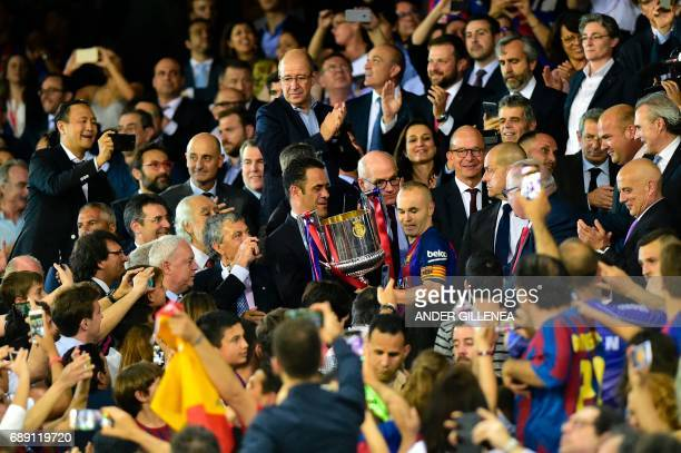 Barcelona's midfielder Andres Iniesta receives the trophy after the team won the Spanish Copa del Rey final football match FC Barcelona vs Deportivo...