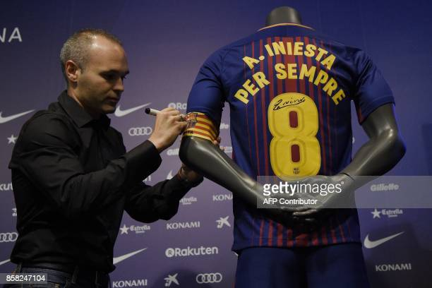Barcelona's midfielder Andres Iniesta signs a special FC Barcelona jersey after renewing his contract at the Camp Nou in Barcelona on October 6 2017...