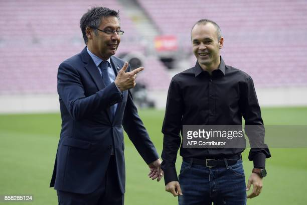 Barcelona's midfielder Andres Iniesta smiles next to the Catalan club's president Josep Maria Bartomeu after renewing his contract at the Camp Nou in...