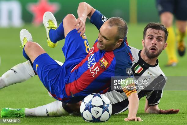 TOPSHOT Barcelona's midfielder Andres Iniesta vies with Juventus midfielder Miralem Pjanic during the UEFA Champions League quarter final first leg...